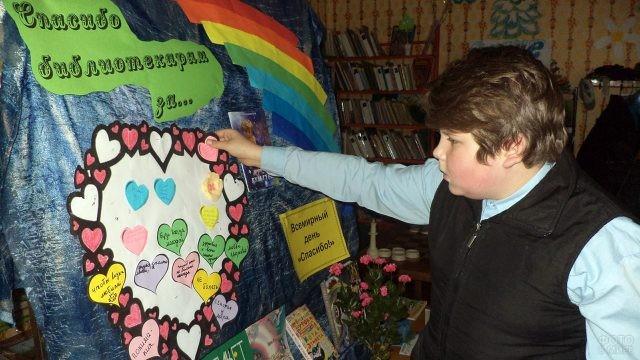 Мальчик клеит стикер со словами благодарности на стенд в библиотеке
