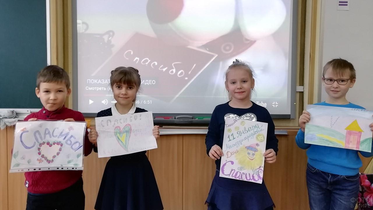 Первоклашки с рисунками со словом Спасибо у доски в классе