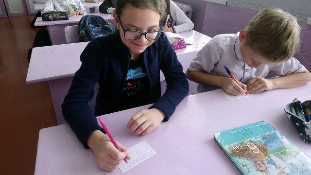 Шестиклассники подписывают карточки со словами благодарности друг другу