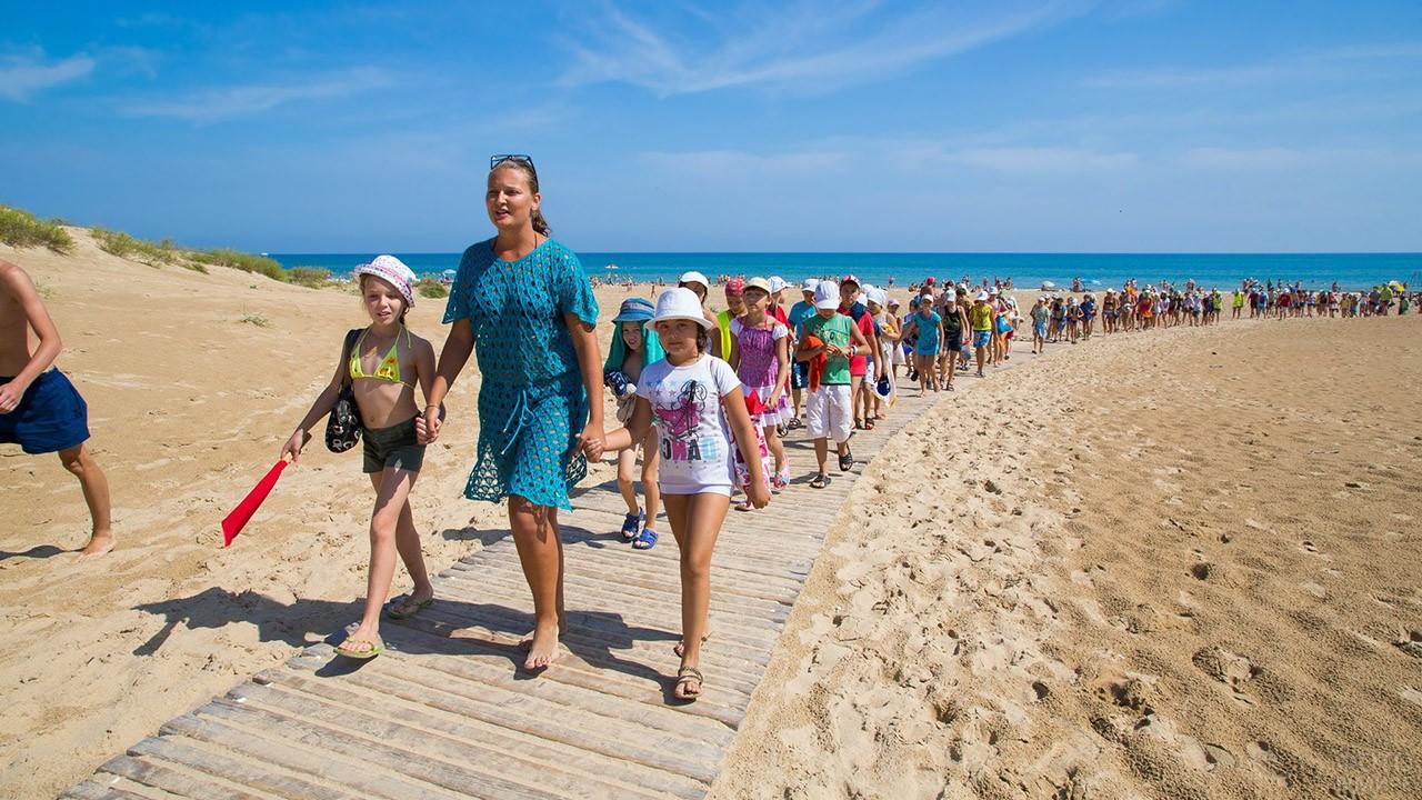 Вожатая летнего лагеря ведёт детей с пляжа