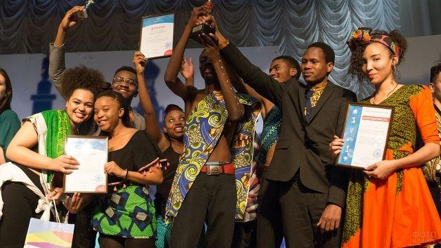 Иностранные студенты в национальных костюмах с наградами и грамотами