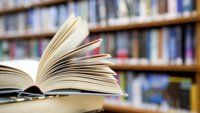 Открытая книга на фоне библиотечного шкафа