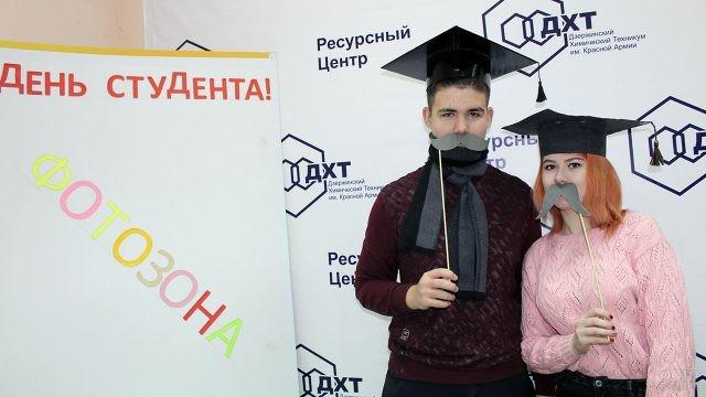 Пара студентов в шуточной самодельной фотозоне