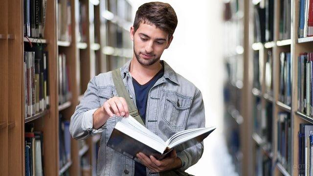 Студент с книгой в библиотеке