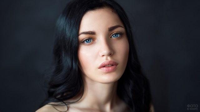 Брюнетка с голубыми глазами на сером фоне