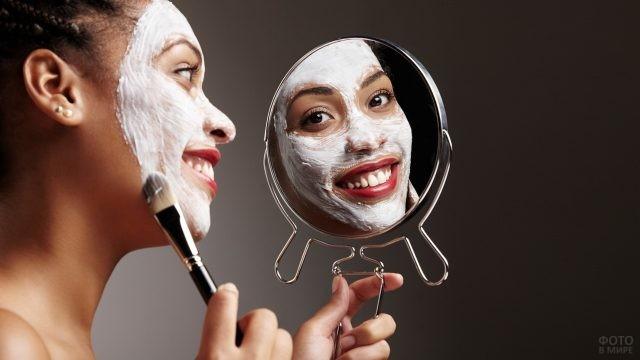 Девушка с косметической маской смотрится в зеркало