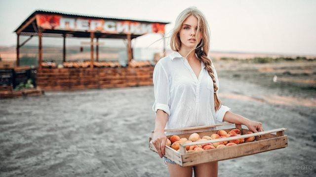 Блондинка держит короб с персиками
