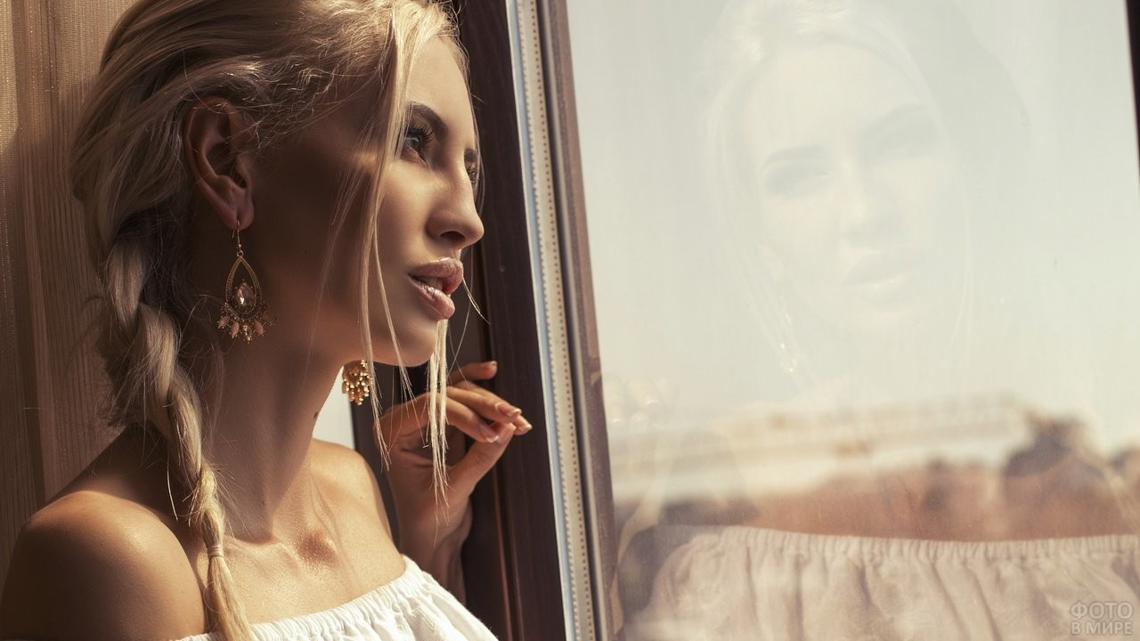 Блондинка с жиденькой косичкой смотрит в окно