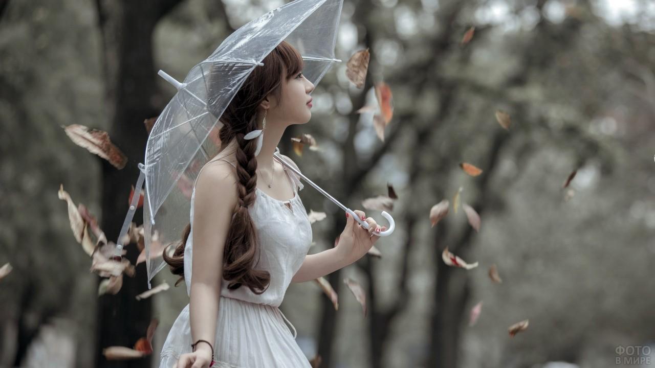 Девушка с двумя косами под зонтом в осеннем лесу