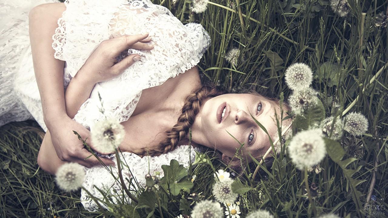 Девушка с косой лежит в окружении одуванчиков
