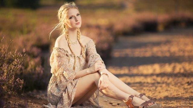 Девушка с жиденькими косками сидит на земле