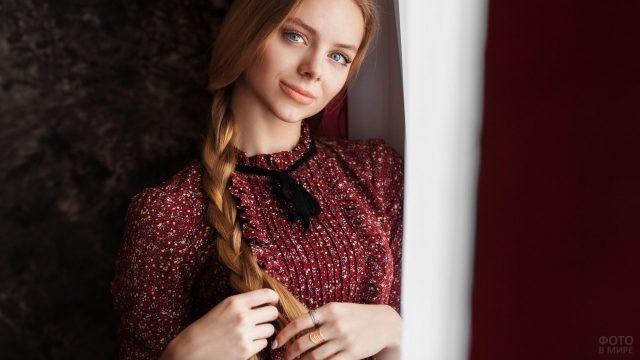 Девушка в бордовом платье плетёт косу