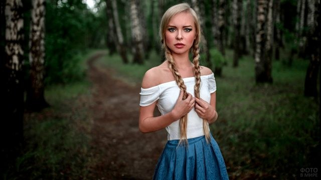 Девушка в лесу держится за две косички