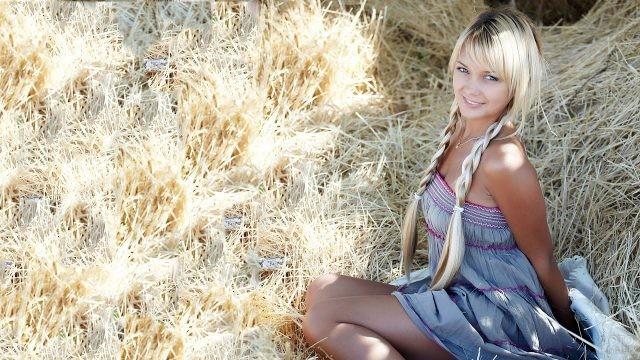 Крашеная блондинка с косами сидит в стогу сена