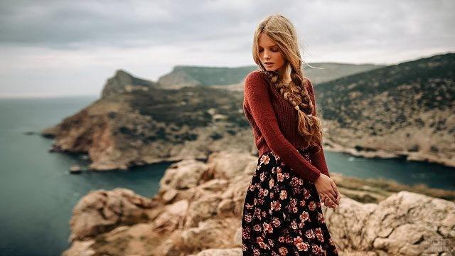 Романтичная девушка с косами на фоне фьорда