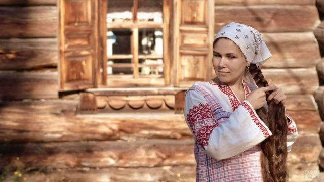 Русская девушка, в наряде со свастичным узором, заплетает косу