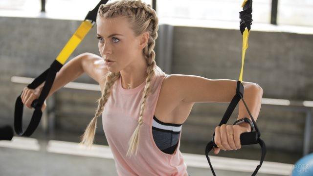 Спортивная блондинка с косичками выполняет упражнение