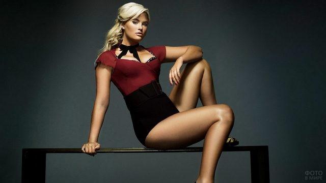 Блондинка с округлыми бёдрами сидит на подставке