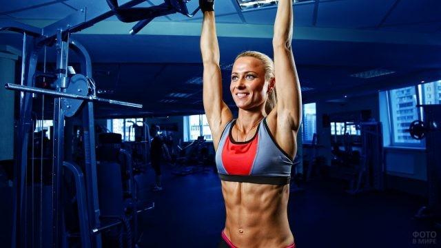 Блондинка спортивного телосложения подтягивается на турнике
