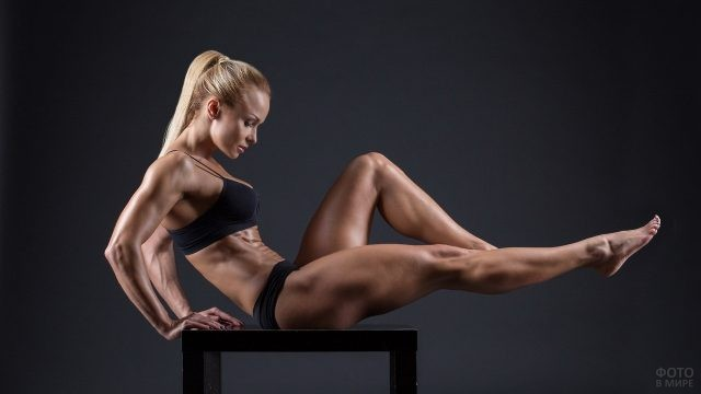 Мускулистая блондинка сидит на табурете