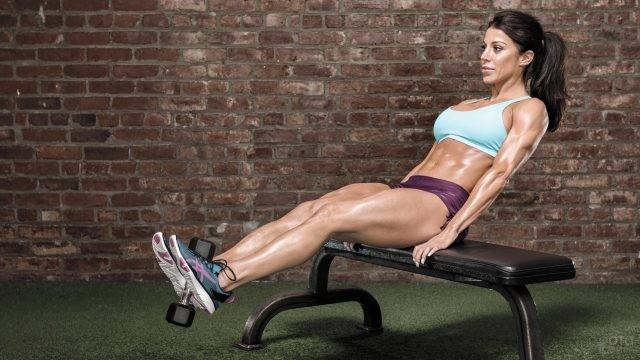 Накаченная девушка выполняет упражнение