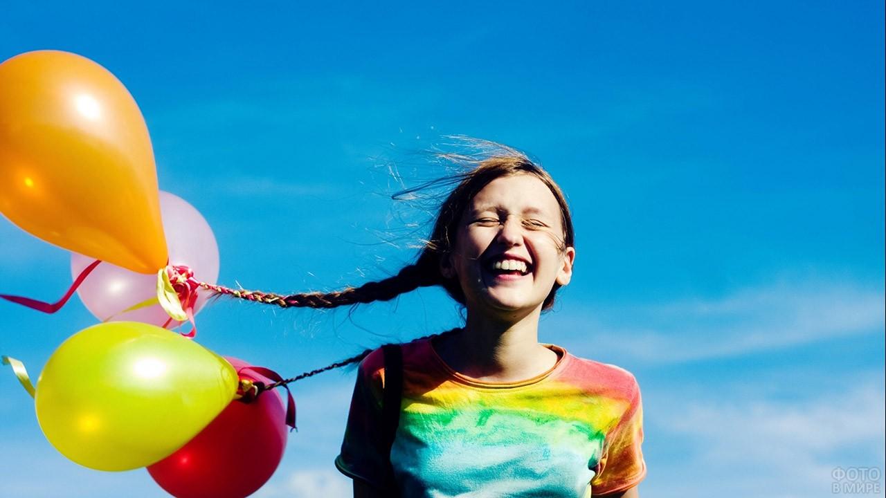 Смеющаяся девочка с шариками, привязанными к косичкам