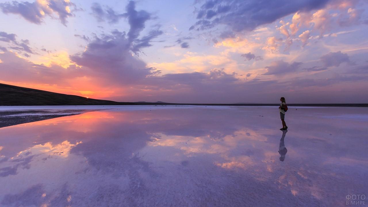 Фигурка туристки на необъятном горизонте крымского побережья на закате дня