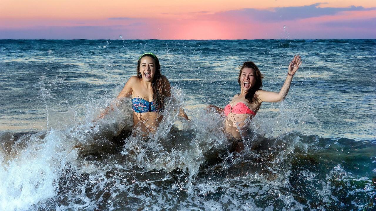 Туристки плещутся в волнах на закате дня