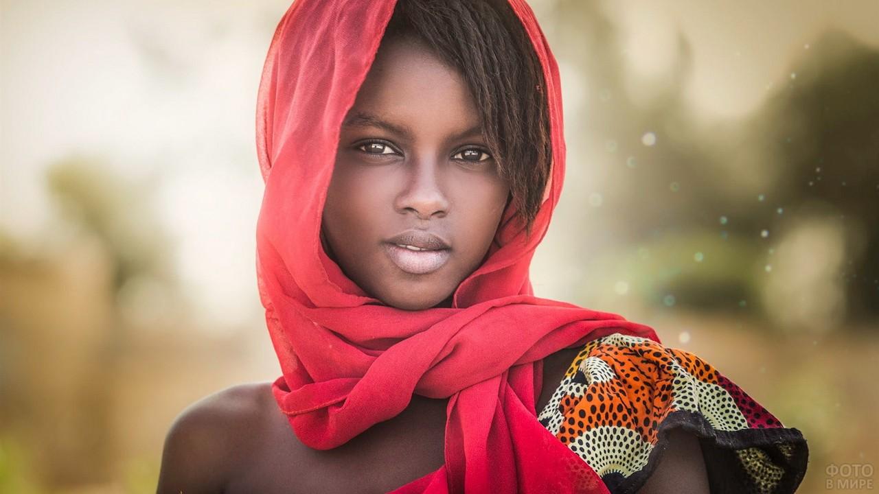 Юная негритянка в красном шарфе на голове