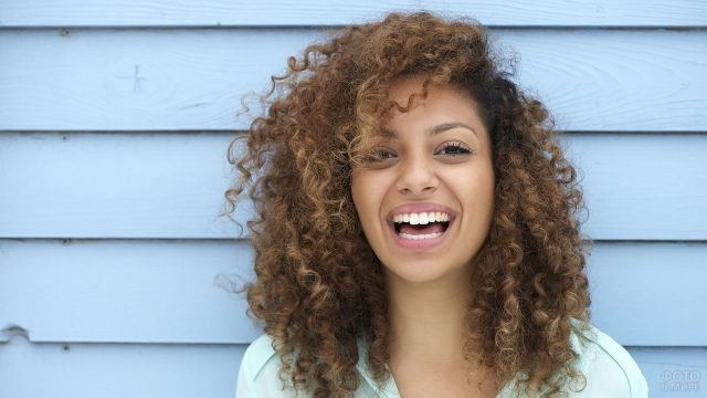 Кудрявая девушка смеётся у стены