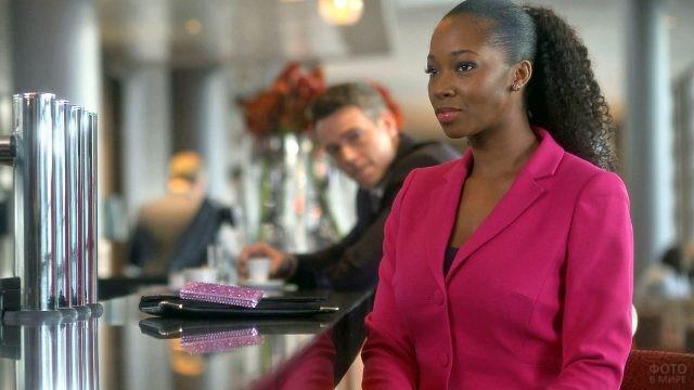 Негритянка в малиновом жакете в кафе