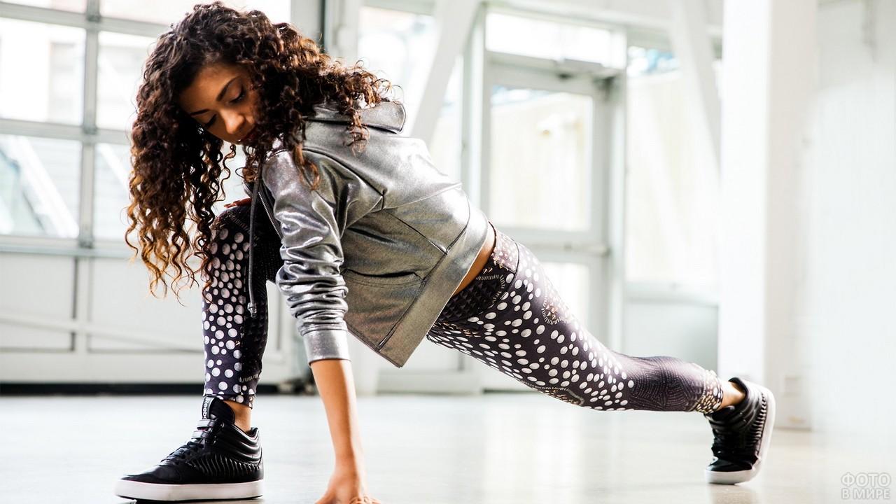 Танцовщица делает растяжку в зале