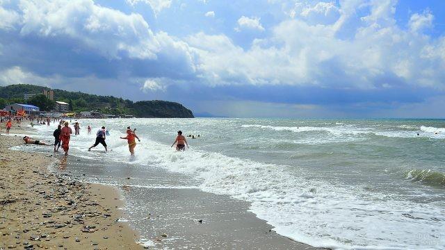 Туристы плещутся в набегающих волнах