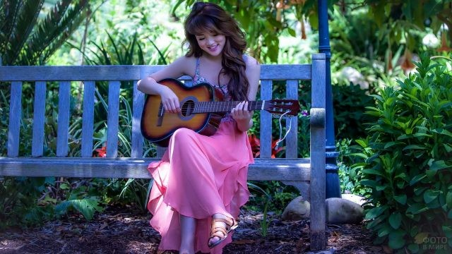Азиатка с гитарой на лавочке в саду