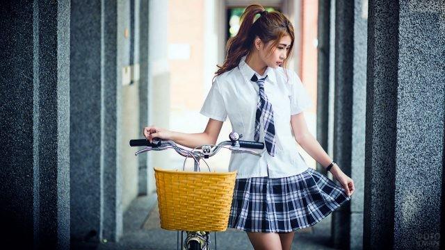 Азиатка стоит возле велосипеда