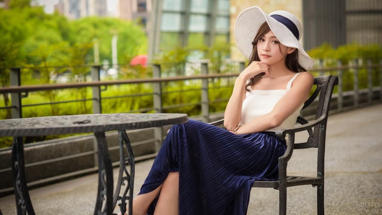 Азиатка в синей юбке за столиком