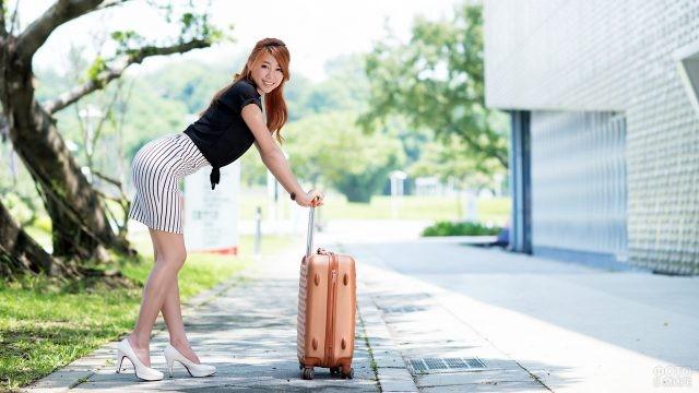 Азиатская девушка с чемоданом