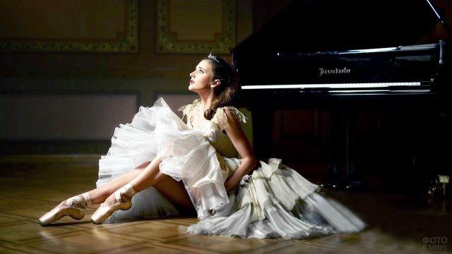 Балерина в пачке сидит возле рояля
