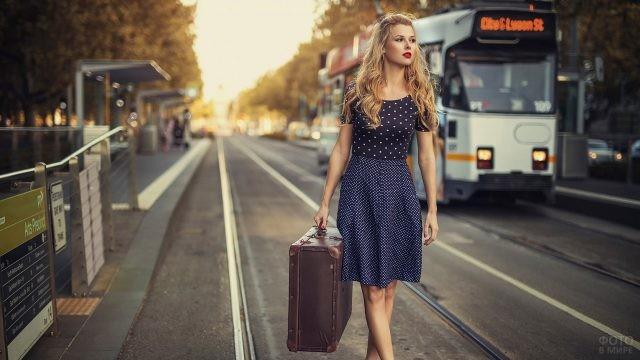 Блондинка с чемоданом идёт по рельсам