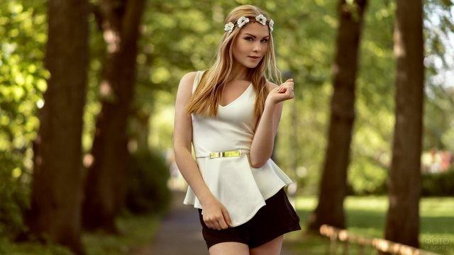 Блондинка с венком на голове фотографируется в парке