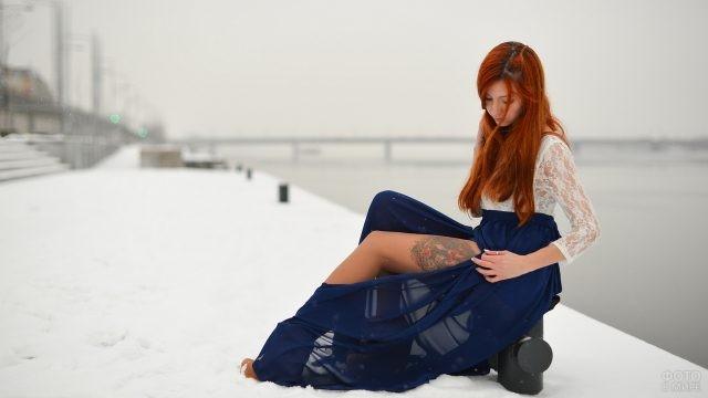 Рыжая девушка в длинной синей юбке