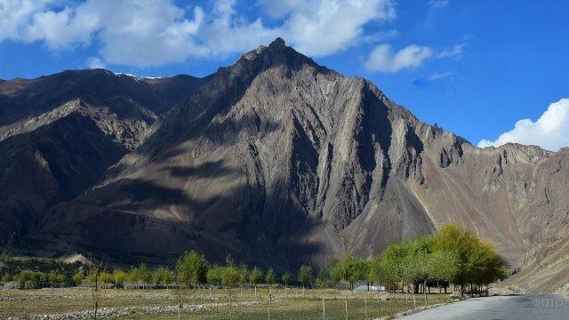 Дорога, обрамлённая высокогорьем