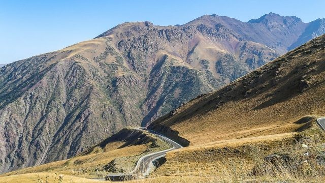Извивающаяся дорога вдоль высоких горных вершин
