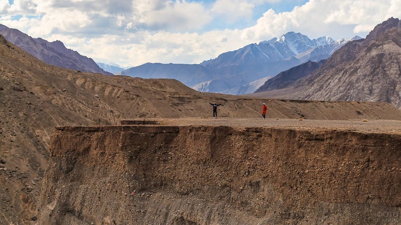 Люди стоят у высокого горного обрыва