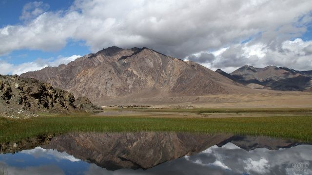 Отражение высоких гор в воде