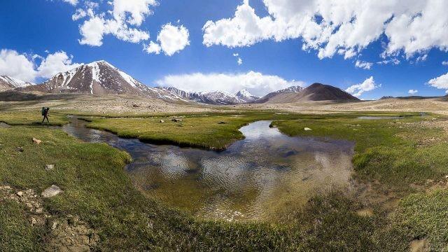 Путешественник идет по берегу небольшой реки вблизи гор