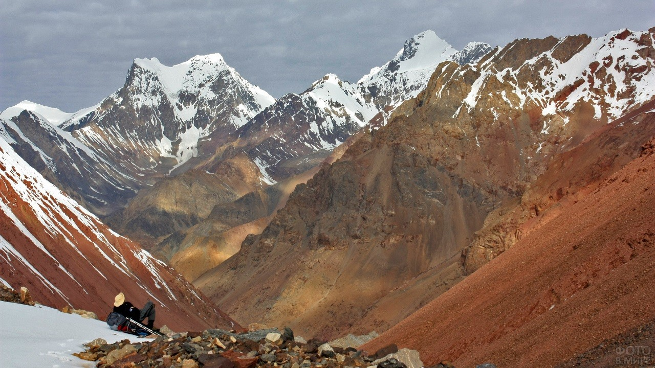 Турист лежит на горе и любуется природой