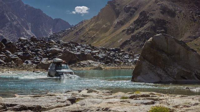 Внедорожник едет по воде на фоне гор