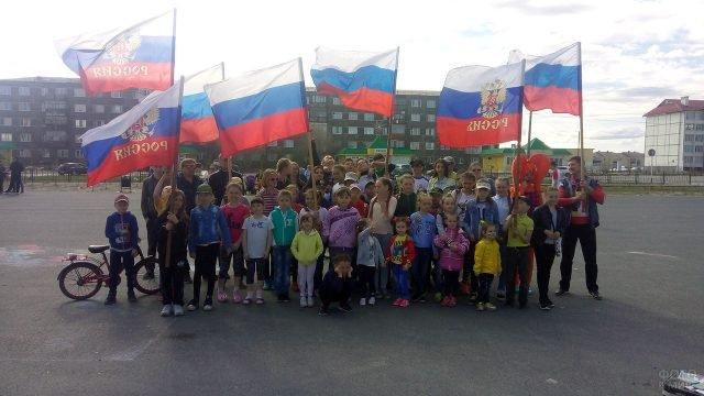 Дети с флагами на улице Нового Уренгоя в День России