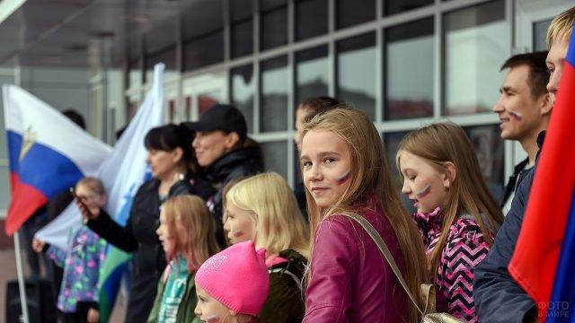 Девчонки-школьницы с триколором на щеках в День России